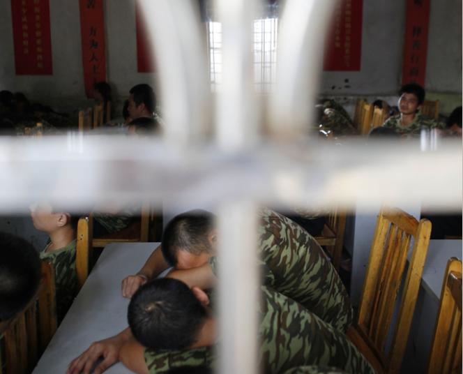 """惠州某处戒""""网瘾""""学校,教官用音乐引导学员们进行冥想,不少学员趴在桌面上沉思。"""