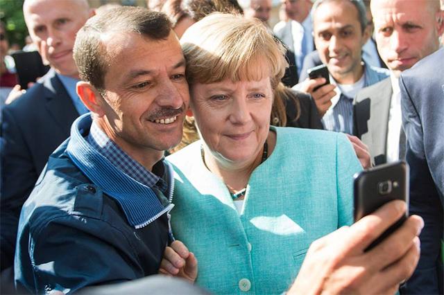 默克尔在柏林一难民接待中心与难民自拍合影