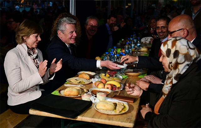 德国总统高克走访柏林穆斯林聚集区,与民众分享开斋小吃,图片来自CFP