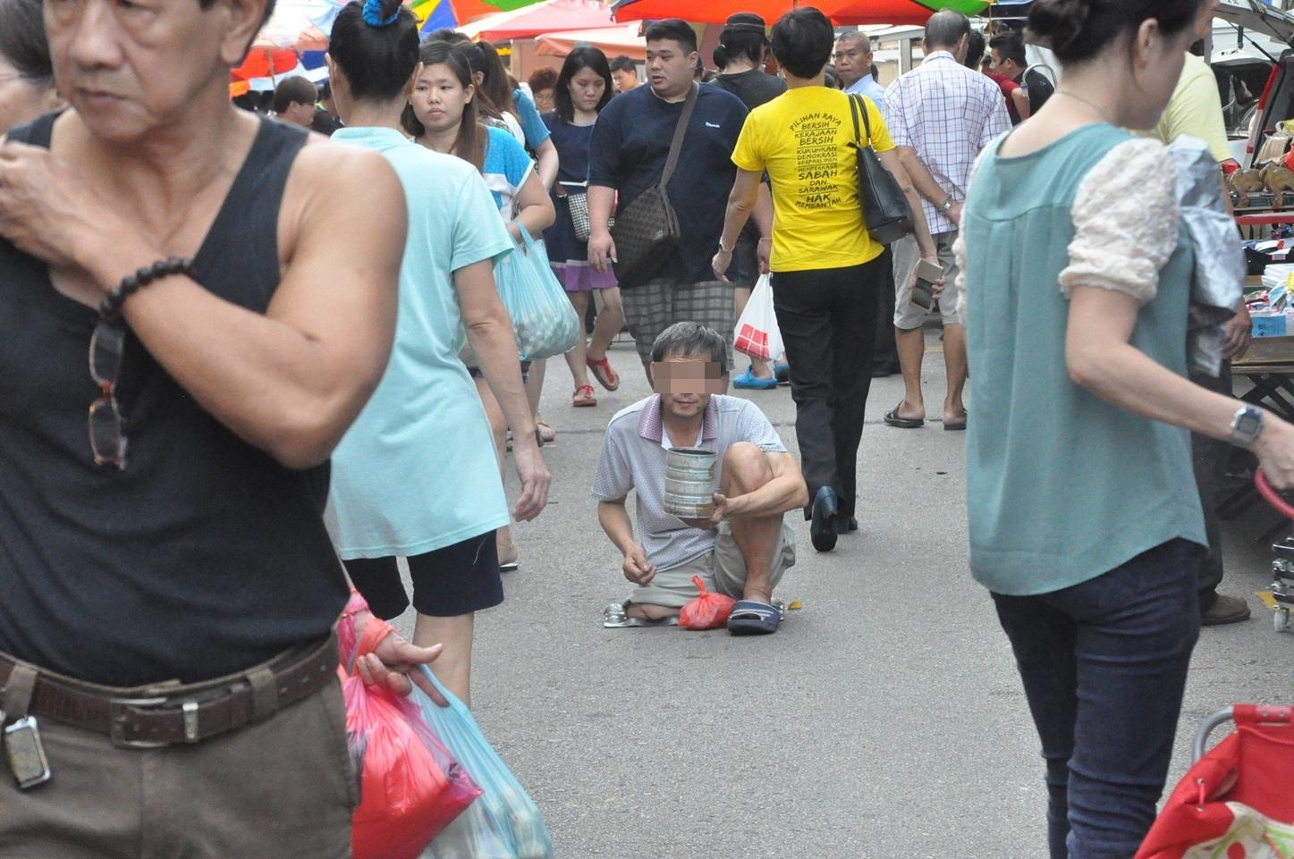 在马来西亚早市出现的残疾人乞丐