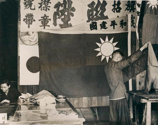 """图:1940年,日占时期广州的制旗铺,正在制作汪伪政权版的""""青天白日旗"""",可以很清晰地看到旗帜上的""""和平建国""""猪尾巴。"""