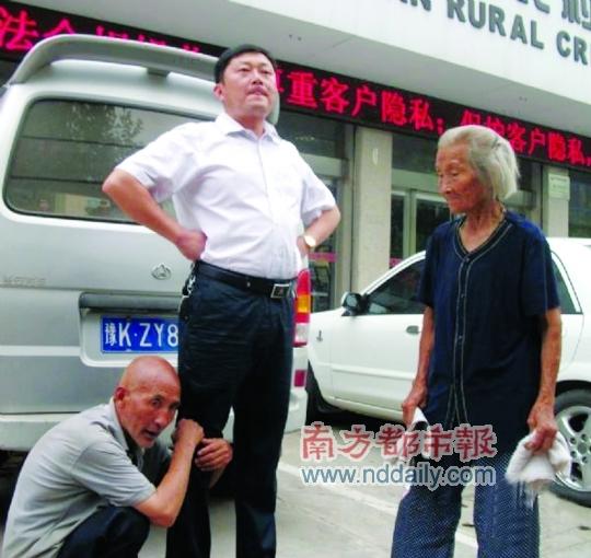 屯里村一名老大爷抱着一名男子大腿,在一处信用社建筑前讨要存款