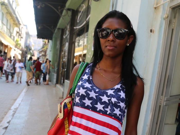 一位哈瓦那街边的古巴女孩,穿着美国国旗图案的T恤