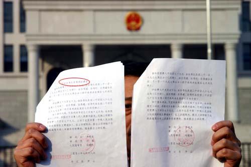 北京石景山法院出具的两份文号相同但内容却有出入的判决书。左侧的判决书上多了一行字(图中画圈处)