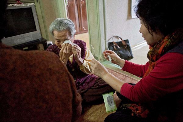 一位义工(右)正在试着宽慰今年89岁在首尔独居的老人尹占桃