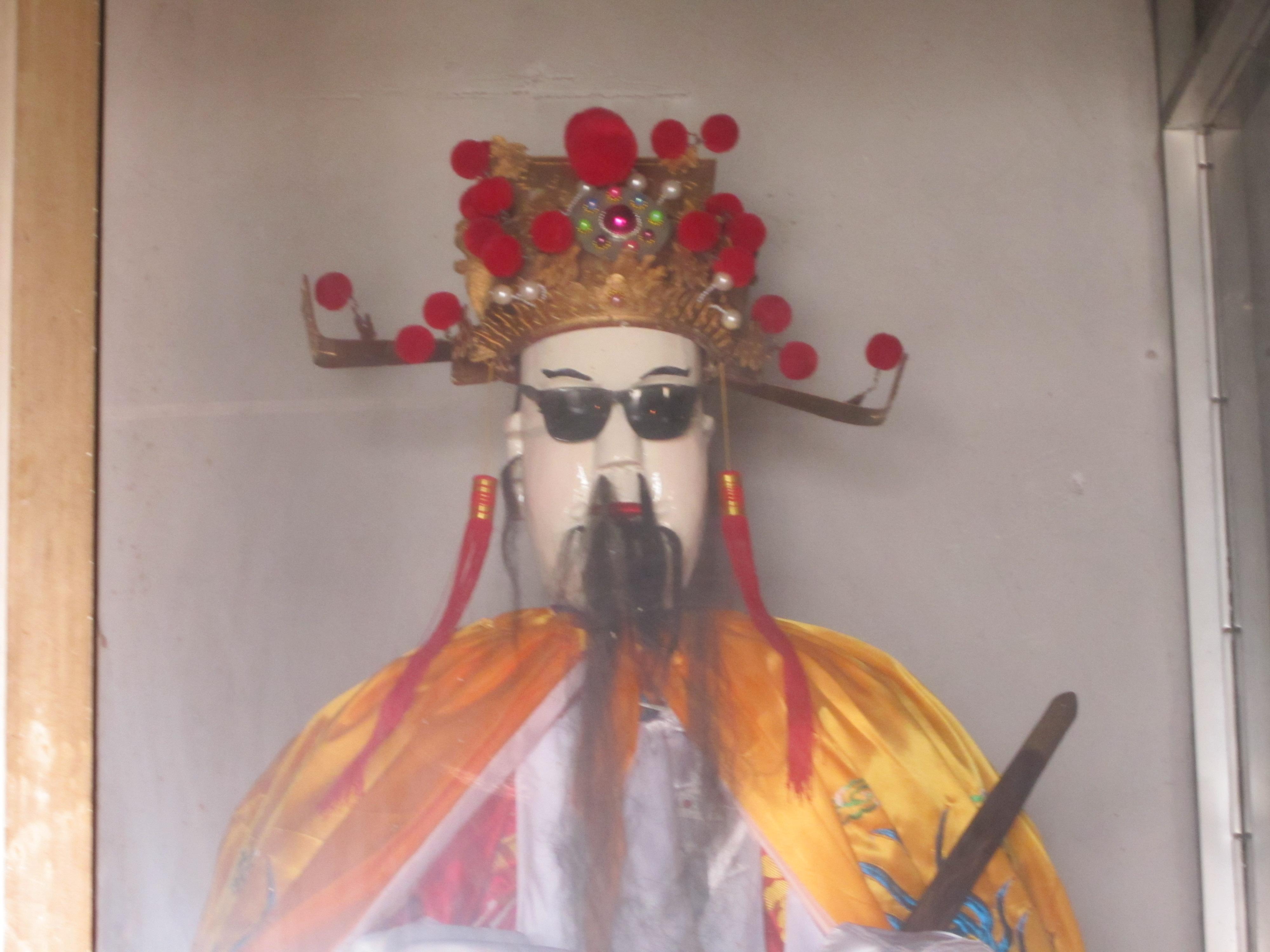 庙祝觉得这尊神像眼睛没有塑出威严,所以给神像戴上了墨镜