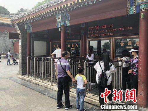 5月10日,北京北海公园门口,一名小女孩正在排队购票