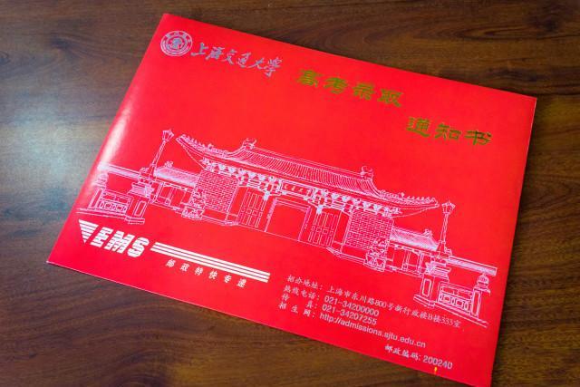 """上海交大录取通知书正面以""""紫气东来门""""为背景,镶嵌""""交通大学""""四个字图片"""
