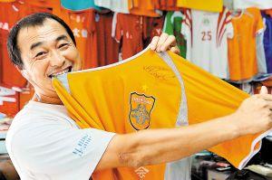 ▲超级球迷简满根收藏了法国球星亨利当年来深圳时给球迷签名的球衣。本报记者 吴峻 摄