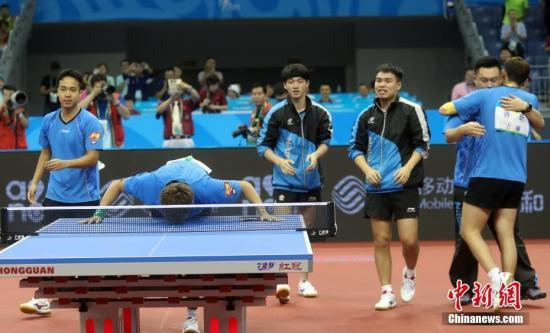9月1日,天津全运会乒乓球男子团体决赛在武清体育馆举行,上海队胜四川队,获得金牌。图为上海队庆祝胜利,赵子豪亲吻球桌。中新社记者 张宇 摄