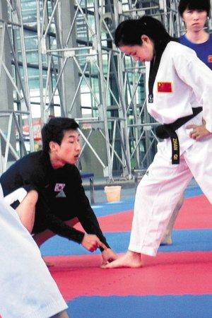 韩国教练金朴贤(左)纠正有望冲击金牌的中国女选手张静静的动作