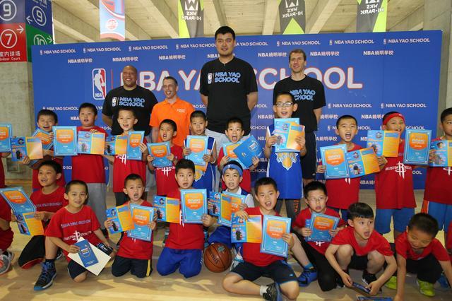 NBA中国CEO舒德伟和姚明及主教练比尔-辛格尔顿与首期毕业的小学员合影