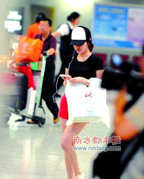 挽著一個大塑料袋的郭美美到達首都機場後,一直在看手機。