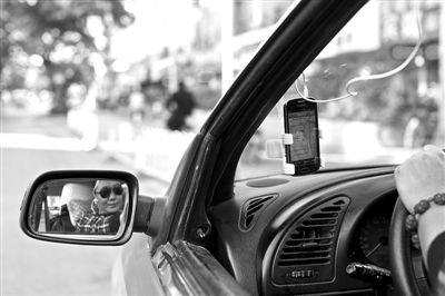 固定在出租车上装有打车软件的手机。目前大部分出租车司机均使用非官方版本打车软件。 新京报记者 周岗峰 摄