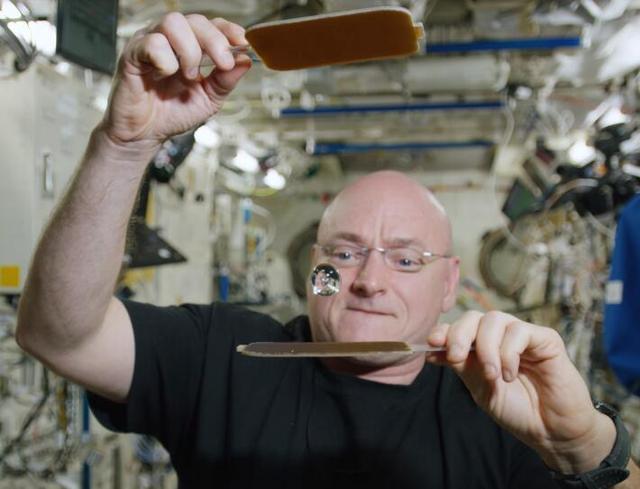 """微重力环境下,流体的表现与地面也不相同。图为NASA航天员Scott Kell在微重力环境下做的水球""""乒乓""""展示。两个拍子击打水球,就像打乒乓球。"""