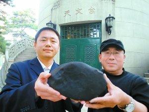 北京天文馆陨石专家张宝林(右)和吴静杰手捧陨石