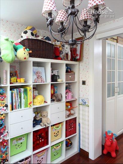 一个整体的收纳柜整齐摆放着孩子们的书籍和玩具