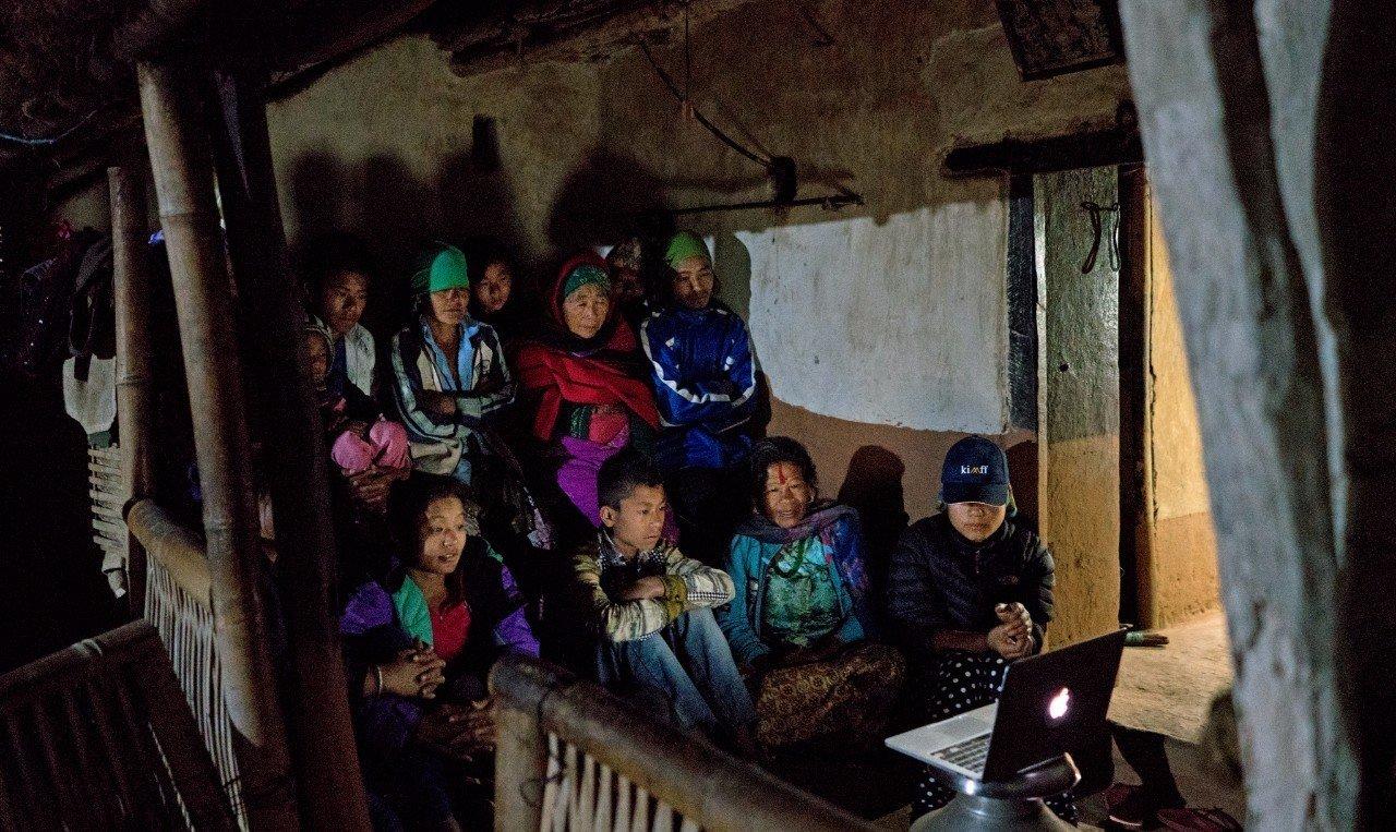 米拉和家人一起观看影片。摄影/Lloyd Belcher