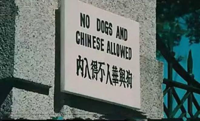 """《精武门》剧照,陈真踢碎写有""""狗与华人,不得入内""""的木牌"""