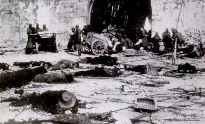 在南京,日本士兵用手推车搬运从商店里抢到的赃物。照片前方是大约五十具被害中国军人和平民的尸体