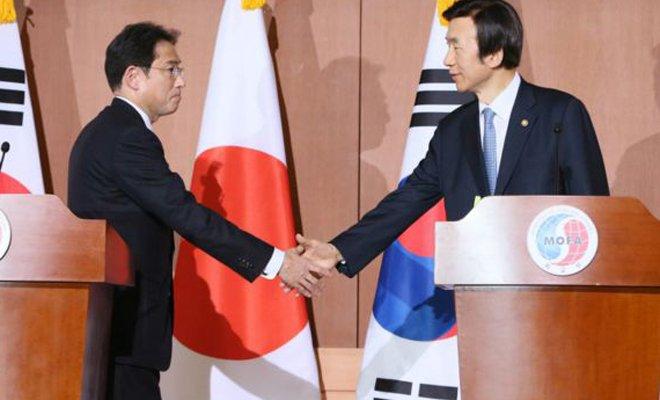 日本外相岸田文雄(左)与韩国外长尹炳世(右)在12月28日的联合记者会上握手