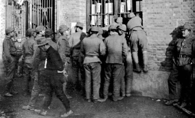 1938年1月,日军在南京开设慰安所,图为日军官兵拥挤在慰安所旁