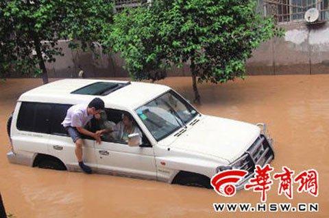 宝鸡市区文化路附近,一辆汽车被淹,车内人想从车窗翻出来高清图片