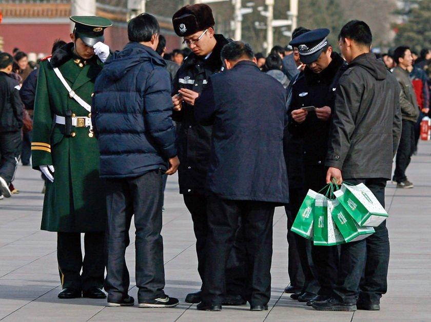 """3月2日,在天安门周边巡逻的警察在检查过往路人证件。全国""""两会""""期间,北京警方将依托环京城的""""护城河行动"""",在3月1日至15日期间分层次启动""""三道防线"""",坚持""""逢疑必查,逢疑必录"""",及时发现并阻止各类危险因素混入北京市。"""