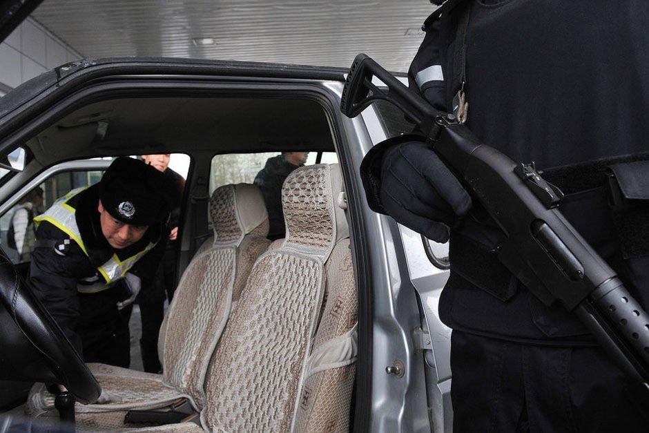 """3月1日,为保证全国""""两会""""的顺利召开,北京市公安局巡特警在进京的路口进行""""查处管制刀具和危险物品专项行动。 图为警察在白庙检查站对进京车辆进行检查。"""