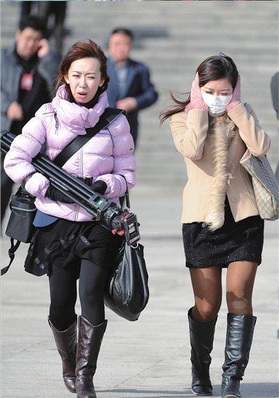 寒冷的春天让衣着单薄的女记者手捂面庞前行。