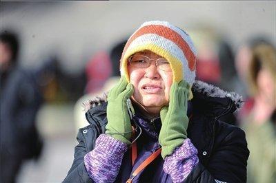 一名女记者在寒风中等待人大代表到场。