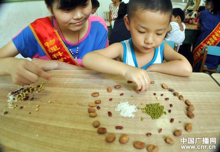 聊城市龙山双语幼儿园与几名小朋友用五谷杂粮摆成笑脸图案让小朋