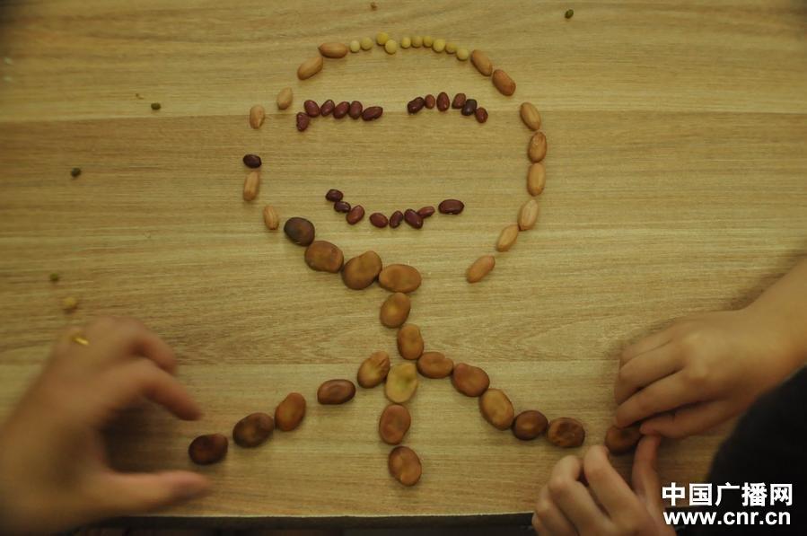 园与几名小朋友用五谷杂粮摆成人形让他们开心认识五谷杂粮.(中