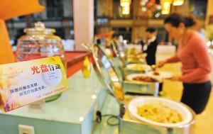 """酒店自助餐区域放有""""光盘行动""""温馨提示,提倡市民按需取餐不要浪费 记图片"""