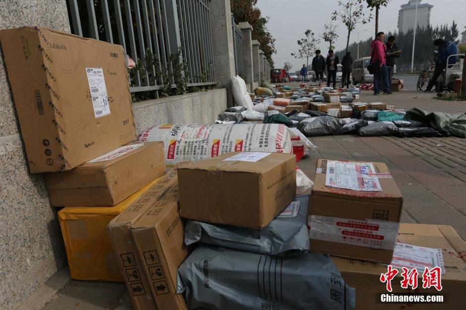 公司的快递员在郑州航空工业管理学院门口分捡成堆的快件.随着