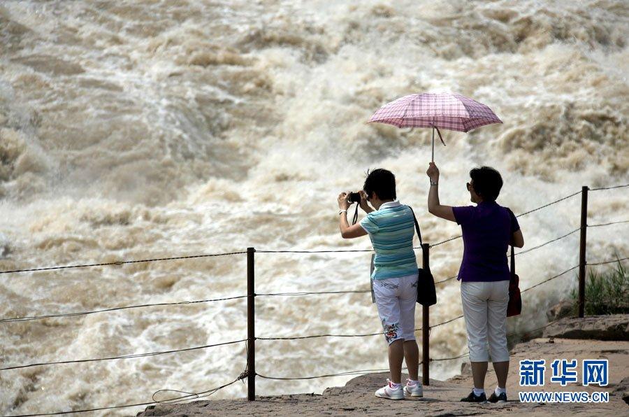 7月17日,游人在黄河壶口瀑布景区观景拍照。新华社发(薛俊摄)