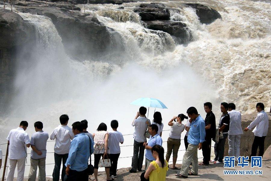 7月17日,游人在黄河壶口瀑布景区观赏美景。新华社发(薛俊摄)