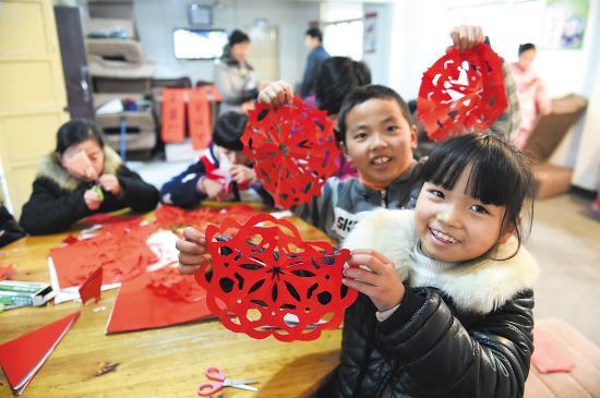 今年9岁留守儿童牟幸如和小朋友们一起展示自己剪的窗花.