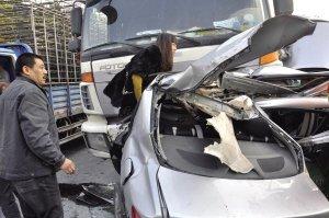 搅拌车撞断小轿车 妈妈爬出车头儿子卡在车内