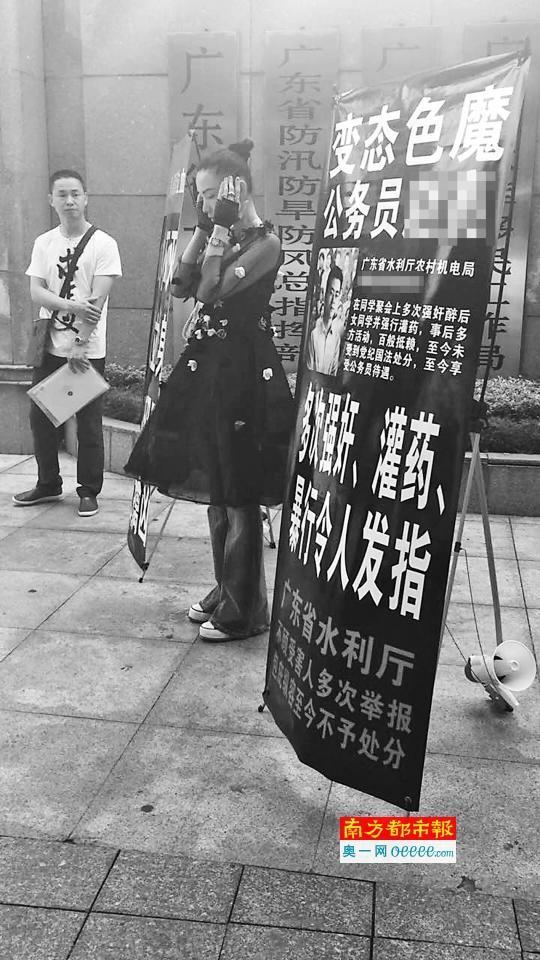 """昨日上午,陈某在广东省水利厅门前拉起横幅""""讨说法""""。受访者供图"""