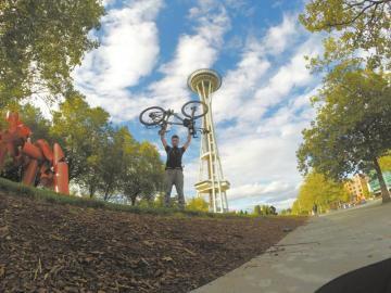 抵達終點后,宣華杰舉著自行車在西雅圖太空針下留影。